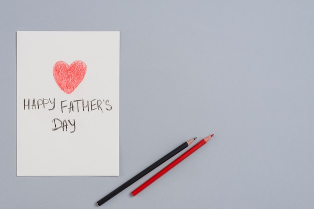 Feliz dia dos pais inscrição na folha de papel com lápis Foto gratuita