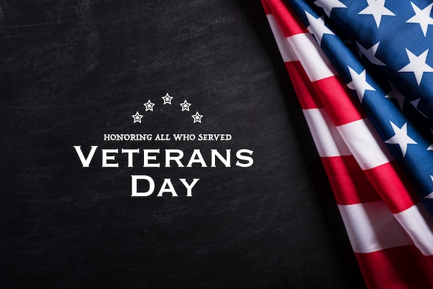 Feliz dia dos veteranos. bandeiras americanas contra um fundo de quadro-negro. Foto Premium