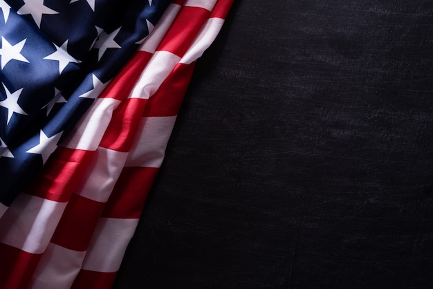 Feliz dia dos veteranos. veteranos das bandeiras americanas contra um fundo do quadro-negro. Foto Premium