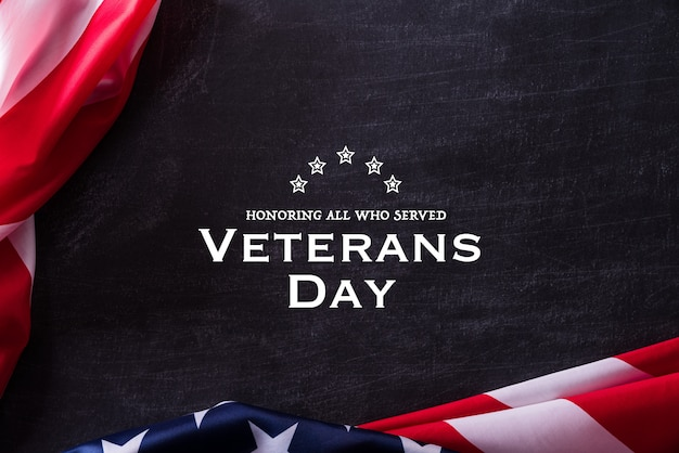 Feliz dia dos veteranos. veteranos das bandeiras americanas contra um quadro-negro. Foto Premium