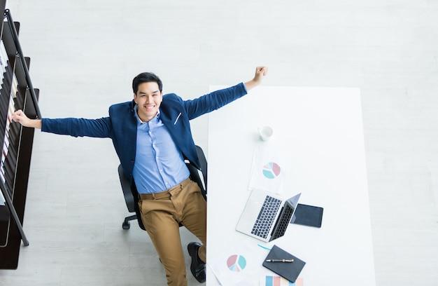 Feliz do bem sucedido empresário jovem asiático no computador portátil Foto Premium