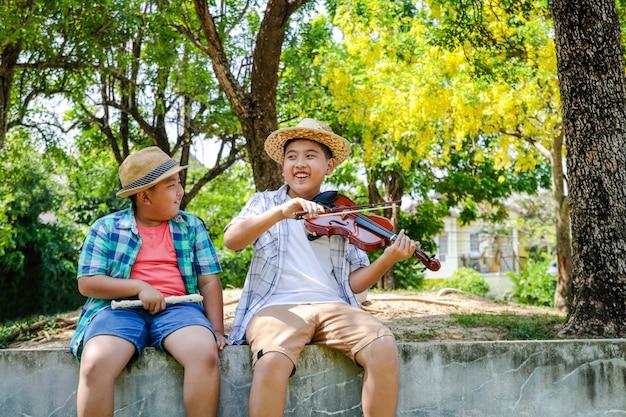 Feliz, dois meninos sorrindo e rindo, tocando música, violinos e flautas no quintal Foto Premium
