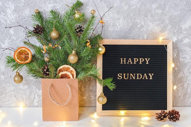 Feliz domingo texto no quadro de letra preto e festivo buquê de ramos de abeto com decoração de natal Foto Premium