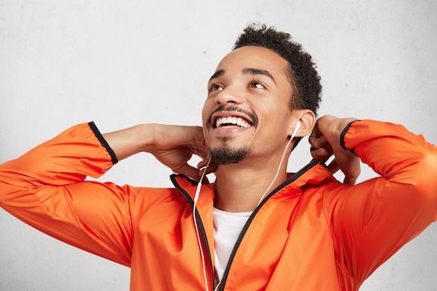 Feliz e animado jovem esportista usa jaqueta, olha para cima com um sorriso, ouve música como se fosse correr de longa distância. Foto gratuita