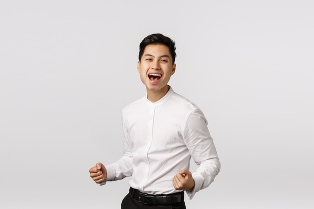 Feliz e bem-sucedido jovem empresário asiático cerra os punhos, acelera e sorri satisfeito, diga sim, comemorando a vitória, fez uma boa oferta, alcance a meta, regozija-se com o prêmio, Foto Premium