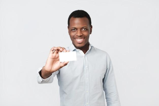 Feliz e bonito empresário afro-americano mostrando o cartão de visita ao cliente Foto Premium