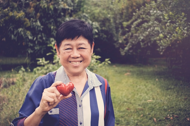 Feliz e saudável mulher sênior asiática segurando coração vermelho em um jardim Foto Premium