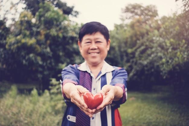 Feliz e saudável, natural, olhar asiático sênior, mulher, segurando, coração vermelho, em, um, jardim Foto Premium