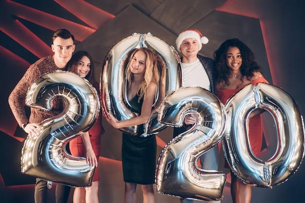 Feliz e sorridente. grupo de jovens amigos lindos com números infláveis nas mãos comemorando o novo ano de 2020 Foto Premium