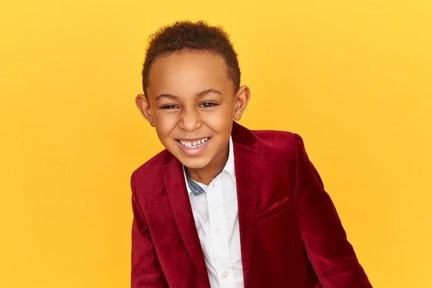 Feliz e travesso adorável garoto negro africano em uma elegante jaqueta de veludo, de bom humor, rindo de histórias engraçadas, piadas ou pegadinhas Foto gratuita
