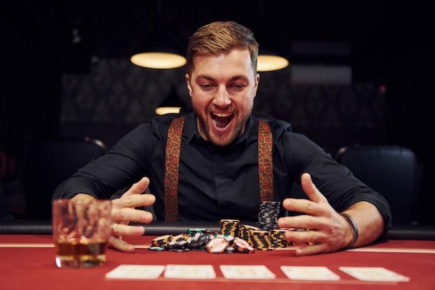 Feliz Elegante Jovem Senta Se No Cassino E Comemora Sua Vitoria No Jogo De Poker Foto Premium
