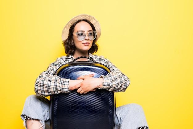 Feliz elegante viajante feminina com chapéu de palha em pé e bolsa de rodas Foto gratuita