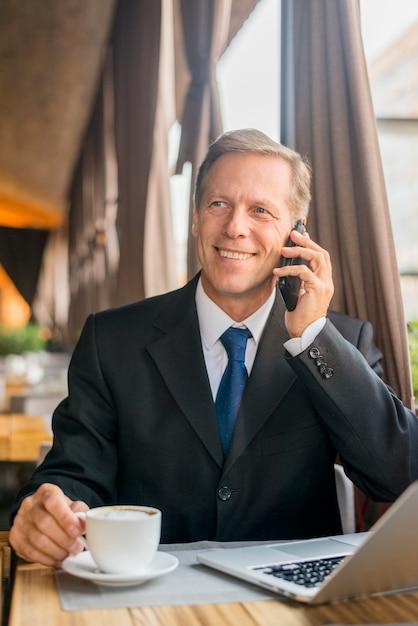 Feliz empresário maduro falando no celular com xícara de café e laptop na mesa Foto gratuita