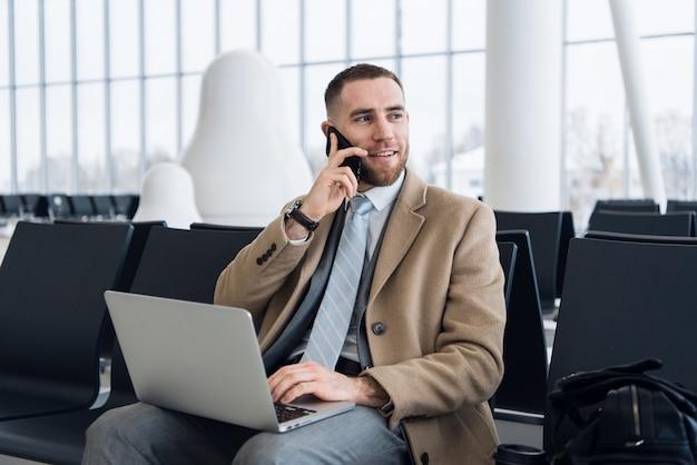 Feliz empresário trabalhando no laptop e falando no celular na sala de espera do aeroporto. empresário caucasiano bonito na sala de espera no terminal do aeroporto Foto Premium