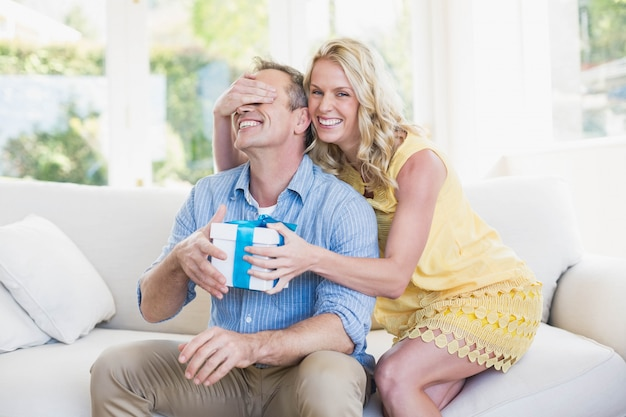 Feliz, esposa, dar, presente, para, marido, em, a, sala de estar Foto Premium