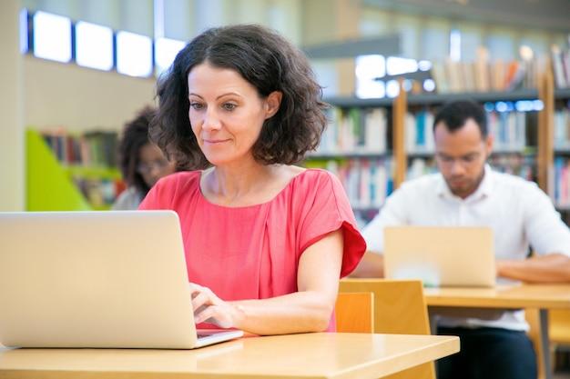 Feliz estudante adulto feminino passando teste on-line Foto gratuita