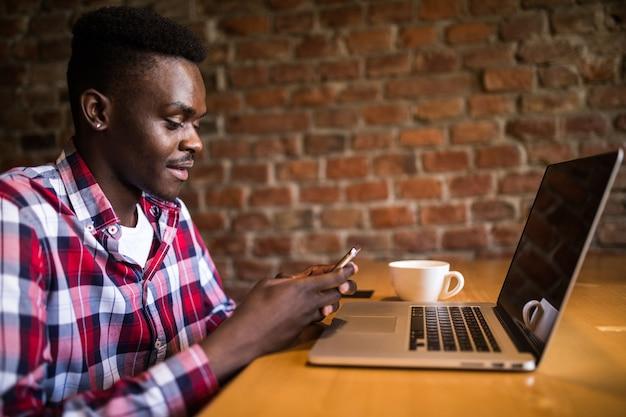 Feliz estudante universitário afro-americano com um sorriso fofo digitando mensagem de texto no telefone, sentado em um café Foto gratuita