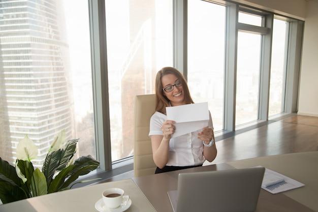 Feliz, executiva, segurando, documento negócio, leitura, boa notícia, em, letra Foto gratuita
