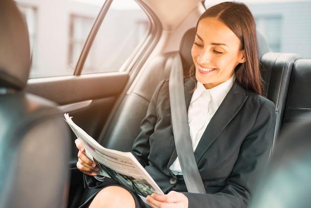 Feliz, executiva, sentando, dentro, carro, leitura, jornal Foto gratuita