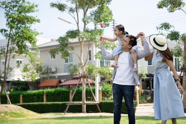 Feliz família asiática. o pai deu sua filha nas costas em um parque sob luz solar natural e casa. conceito de férias em família Foto Premium