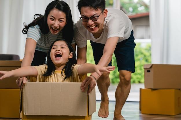 Feliz família jovem asiática se divertindo rindo movendo-se para nova casa. os pais japoneses mãe e pai sorrindo ajudando animado menina andando sentado em caixa de papelão. nova propriedade e realocação. Foto gratuita