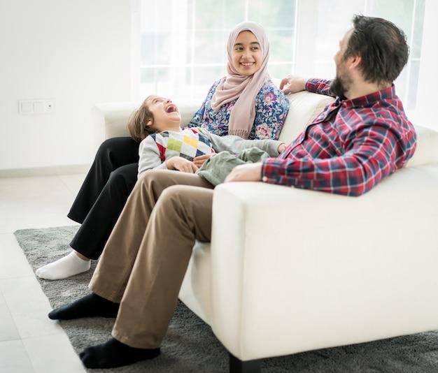 Feliz família muçulmana, sentado no sofá na sala de estar em casa Foto Premium