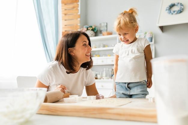 Feliz filha e mãe cozinhando juntos Foto gratuita