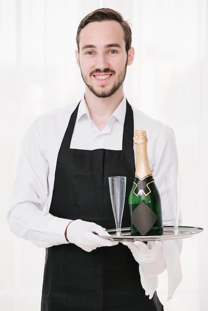 Feliz, garçom, segurando bandeja, com, champanhe Foto gratuita