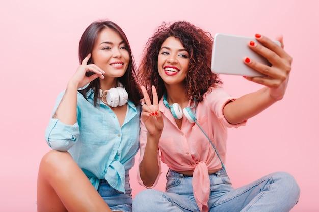 Feliz garota africana com rosto bonito, posando com o símbolo da paz perto de uma encantadora amiga. mulher mulata aforável em jeans e camisa rosa, fazendo selfie com elegante senhora hispânica. Foto gratuita