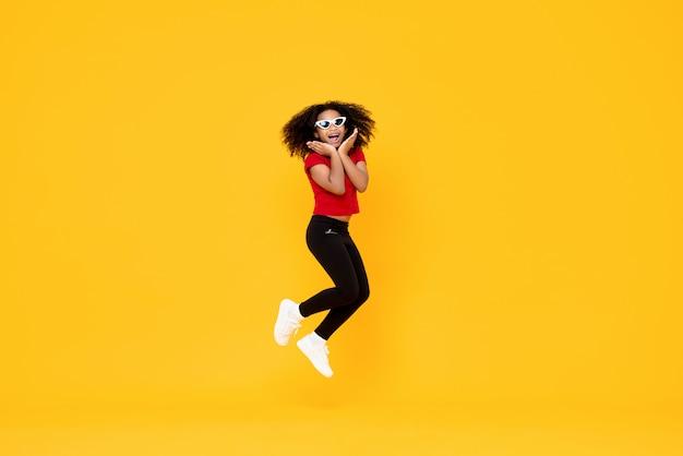 Feliz garota afro-americana elegante pulando no ar com as mãos no queixo isolado na parede amarela Foto Premium