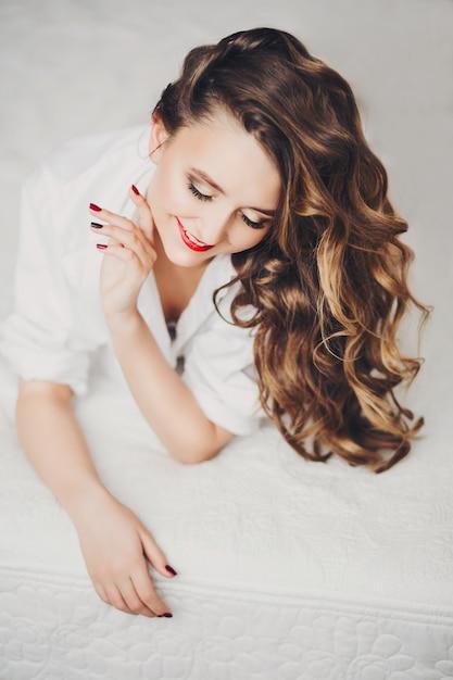 Feliz garota bonita com cabelo morena brilhante e maquiagem sorrindo para baixo. Foto Premium