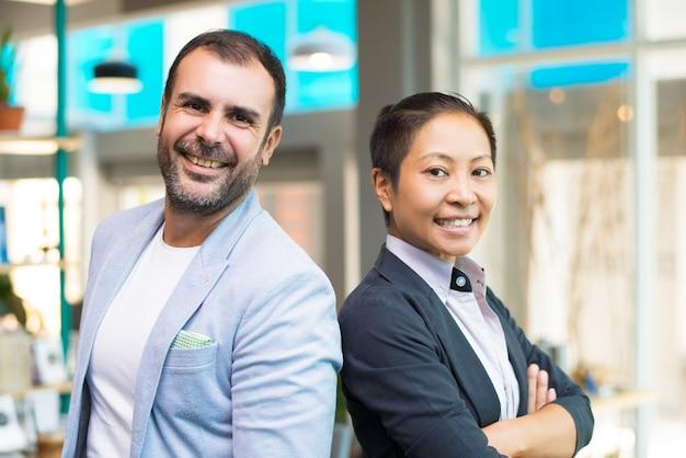Feliz gestores asiáticos e latinos sorrindo e em pé lado a lado Foto gratuita