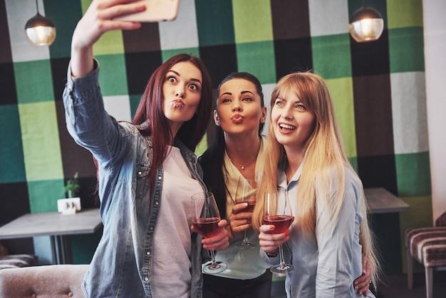 Feliz grupo de amigos com vinho tinto tomando selfie Foto Premium