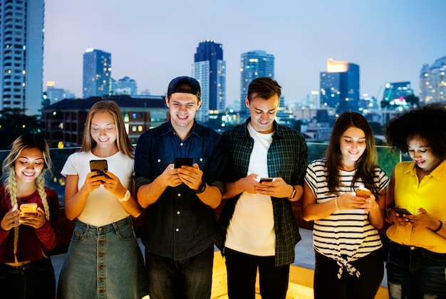 Feliz grupo de jovens adultos usando smartphones na paisagem urbana Foto Premium
