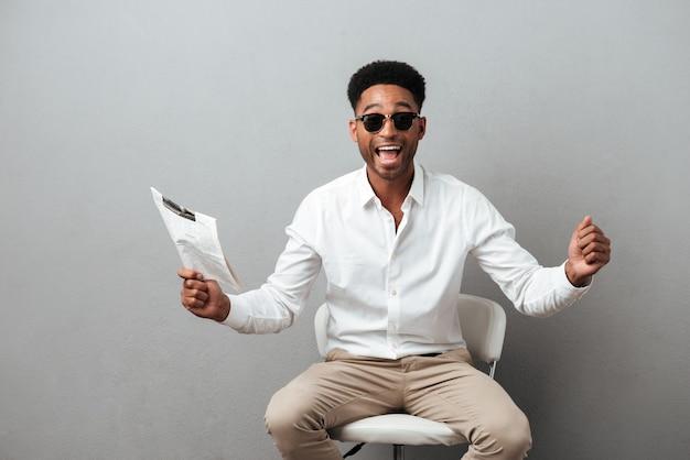 Feliz homem africano animado, segurando o jornal Foto gratuita