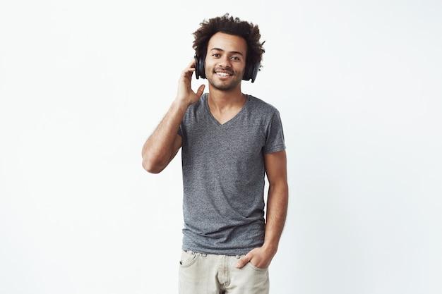 Feliz homem africano em fones de ouvido sorrindo Foto gratuita