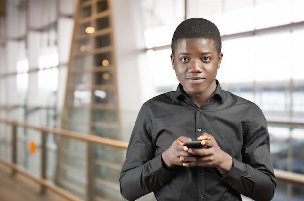 Feliz homem afro-americano usando um telefone celular Foto Premium