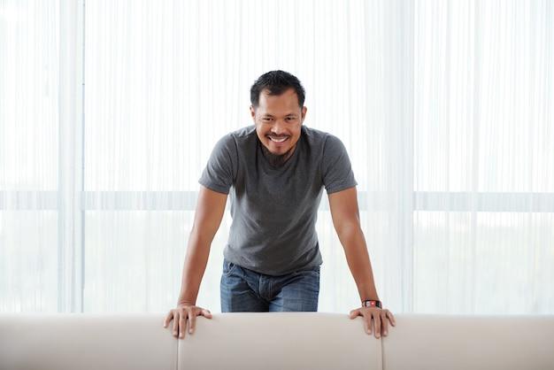 Feliz homem asiático em pé atrás do sofá, apoiando-se nele e sorrindo para a câmera Foto gratuita