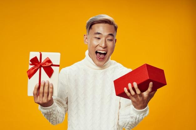Feliz homem asiático em roupas de inverno quente, abrindo um presente Foto Premium