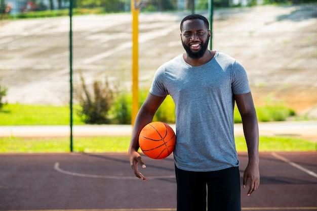 Feliz homem barbudo na quadra de basquete Foto gratuita