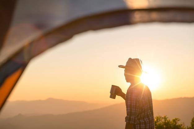 Feliz, homem, com, xícara café segurando, ficar, perto, barraca, ao redor, montanhas Foto gratuita