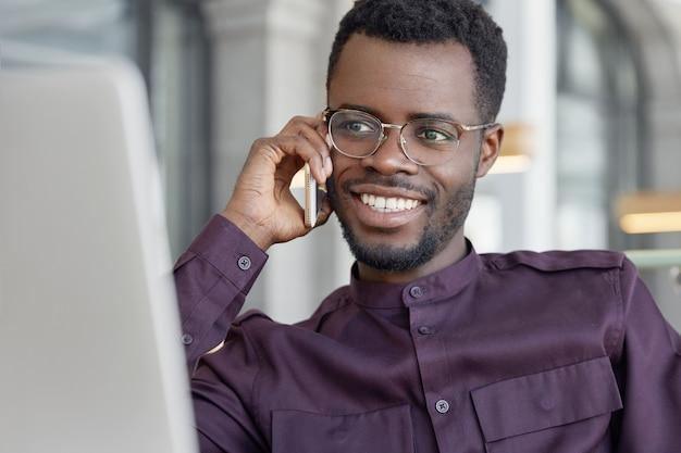 Feliz, homem de negócios africano de meia-idade, conversa agradável com um amigo por meio do smartphone e compartilha o sucesso no aumento das vendas Foto gratuita