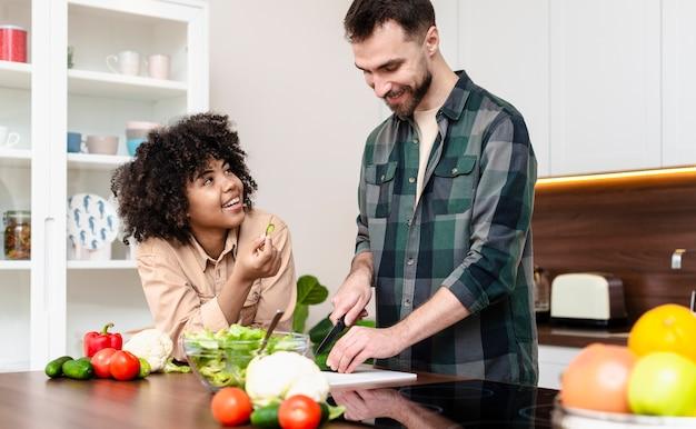 Feliz homem e mulher cozinhando juntos Foto gratuita