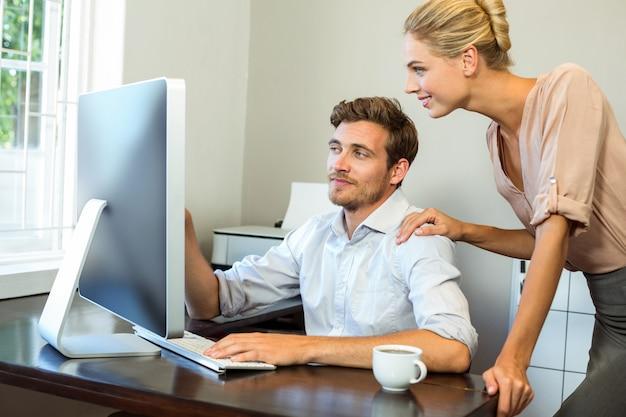 Feliz homem e mulher discutindo enquanto trabalha no computador no escritório Foto Premium