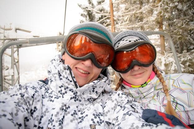 Feliz homem e mulher em óculos de esqui sobe no elevador nas montanhas dos cárpatos. fechar-se. natureza do inverno. Foto Premium