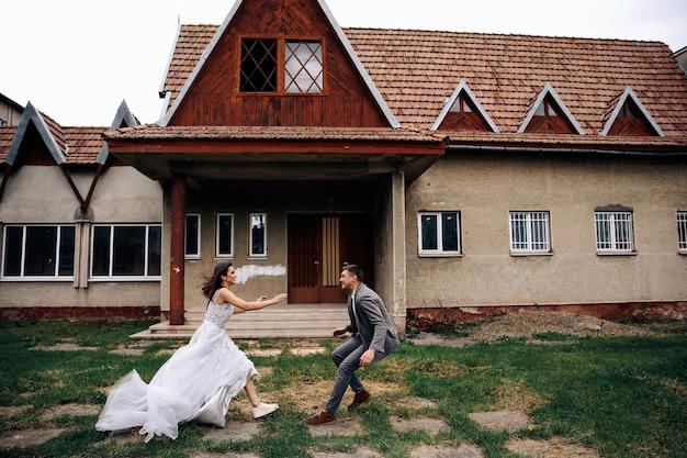 Feliz homem e mulher vestida com roupas oficiais na frente do antigo prédio aconchegante correndo Foto gratuita