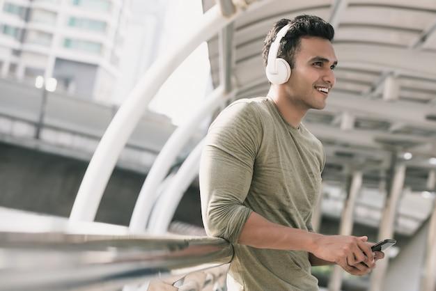 Feliz homem indiano bonito usando fones de ouvido, ouvindo música Foto Premium