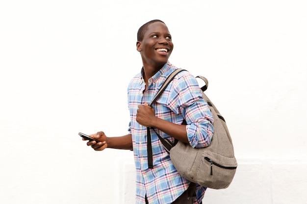 Feliz, homem jovem, andar, com, saco, e, telefone móvel, contra, fundo branco Foto Premium