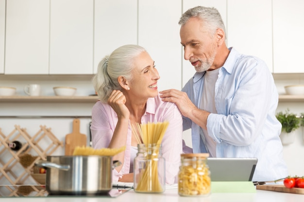 Feliz homem maduro em pé perto de mulher madura alegre usando tablet Foto gratuita