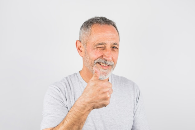 Feliz homem mais velho piscando e mostrando como Foto gratuita